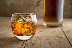 Whisky glass and bottle golden brown ice on wooden surface in saloon bar pub Stock Photos