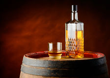 Whisky glass and bottle. Still-life with one whisky glass and one whisky bottle in a cellar on a rustic wooden barrel Stock Image