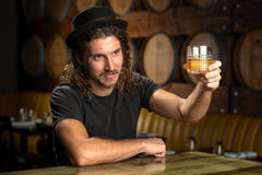 Whisky glass cheers stylish man drinking bourbon at a whiskey distillery restaurant bar. A male holding a Whisky glass gives cheers. A stylish man drinking craft stock photos