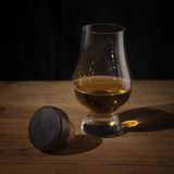Whisky glass and cork on wooden table Royalty Free Stock Photo