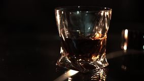 Whisky in a glass on glass table and dark background, selective focus. Royalty Free Stock Image