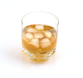 Whisky glass with ice. Close up of a glass of whisky with ice cubes on a white glossy background Royalty Free Stock Photography