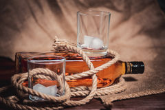 Whisky glass with ice, a bottle of whiskey and a rope Stock Photos