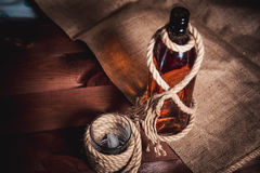 Whisky glass with ice, a bottle of whiskey and a rope Royalty Free Stock Photo