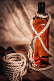 Whisky glass with ice, a bottle of whiskey and a rope Royalty Free Stock Photos