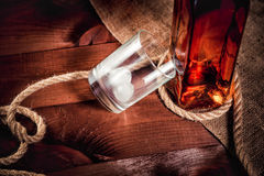 Whisky glass with ice, a bottle of whiskey and a rope Royalty Free Stock Image
