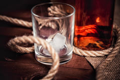 Whisky glass with ice, a bottle of whiskey and a rope Stock Photo