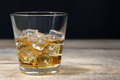 Whisky in glass with ice cubes on wooden board Stock Photos