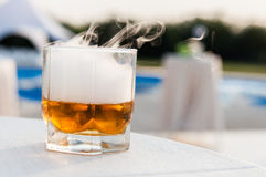 Whisky glass with pool on background. Whisky glass with blue pool on background Royalty Free Stock Photo
