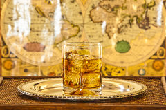 Whisky glass on silver platter on wooden table Stock Image