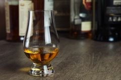Whisky glass with single malt scotch on wooden table and scotch bottles. On the background stock image
