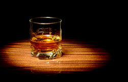 Whisky in a glass. Studio shot of whisky in a glass lit with spotlight  on black Stock Photo