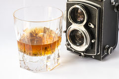 Whisky glass with a vintage camera Royalty Free Stock Image