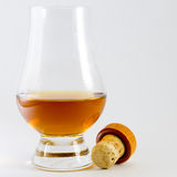 Whisky in a whiskey glass with a cork. A tulip shaped whiskey glass of whisky with a bottle cork lying beside it Royalty Free Stock Photo