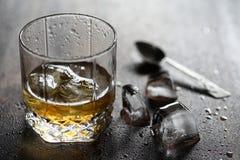 Whisky i ett exponeringsglas och stycken av is på ett trä Royaltyfri Foto
