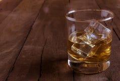 Whisky i exponeringsglas med iskuber på trätabellen Royaltyfri Foto