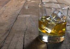 Whisky i exponeringsglas med iskuber på trätabellen Royaltyfria Foton