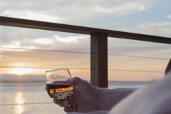 Whisky i hand på solnedgången på däck vid havet Royaltyfria Bilder
