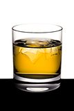 Whisky with ice. The shined glass of whisky with ice stands on a black table Royalty Free Stock Photos