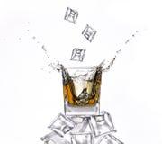 Whisky with ice cubes splashing Stock Photos
