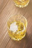 Whisky with ice in two glasses on a wooden background. Toned. Royalty Free Stock Photos
