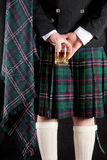 Whisky and kilt. Scotsman holding his glass of whisky behind is kilt Royalty Free Stock Photo