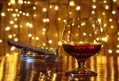 Whisky, konjak, konjak och cigarr på trätabellen Arkivfoton