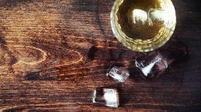 Whisky med is med ett exponeringsglas Kuber av is på en trätabell Royaltyfri Fotografi