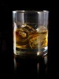 Whisky med is i ett exponeringsglas Arkivbild