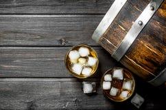 Whisky med is och en trätrumma arkivfoto