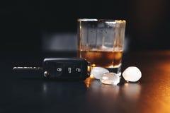 Whisky mit Autoschlüsseln und -handschellen Konzept für das Trinken und das Antreiben lizenzfreies stockfoto