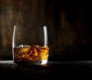 Whisky mit Eis in einem transparenten Glas auf einem hölzernen Hintergrund Stockfotos