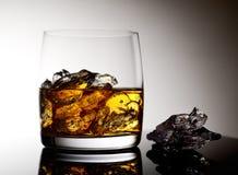 Whisky mit Eis in einem transparenten Glas auf einer Glasoberfläche Stockbild