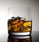 Whisky mit Eis in einem transparenten Glas auf einer Glasoberfläche Stockbilder