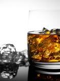 Whisky mit Eis in einem transparenten Glas auf einer Glasoberfläche Lizenzfreies Stockfoto