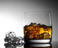 Whisky mit Eis in einem transparenten Glas auf einer Glasoberfläche Lizenzfreies Stockbild