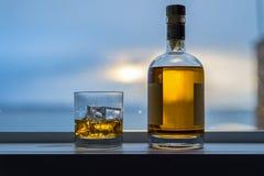 Whisky mit Flasche am Fenster Stockbild