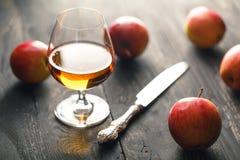 Whisky och äpplen på den mörka trätabellen Fotografering för Bildbyråer