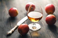Whisky och äpplen på den mörka trätabellen Arkivbilder