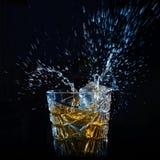 Whisky pluśnięcie od spada kostek lodu Zdjęcia Stock