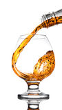 Whisky poured to glass from buttle with splashes. On white Stock Image