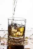 Whisky pouring on ice in glass. Royalty Free Stock Images