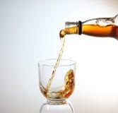 Whisky que es vertido en el vidrio Imagen de archivo libre de regalías