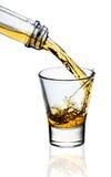 Whisky que es vertido en un vidrio Foto de archivo