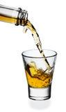 Whisky que es vertido en un vidrio Imagen de archivo