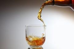 Whisky que es vertido vidrio Imagenes de archivo