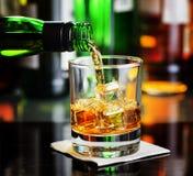 Whisky que vierte un vidrio en una barra fotografía de archivo libre de regalías