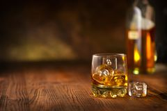 Whisky on the rocks. Glass of whiskey with ice cubes over wooden background. Whisky on the rocks. Glass of whiskey with ice cubes over dark wooden background royalty free stock photo