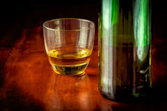 Whisky or rum and a green liquor bottle Royalty Free Stock Photography