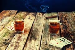 Whisky, sigaar en kaarten op een houten achtergrond Stock Afbeelding